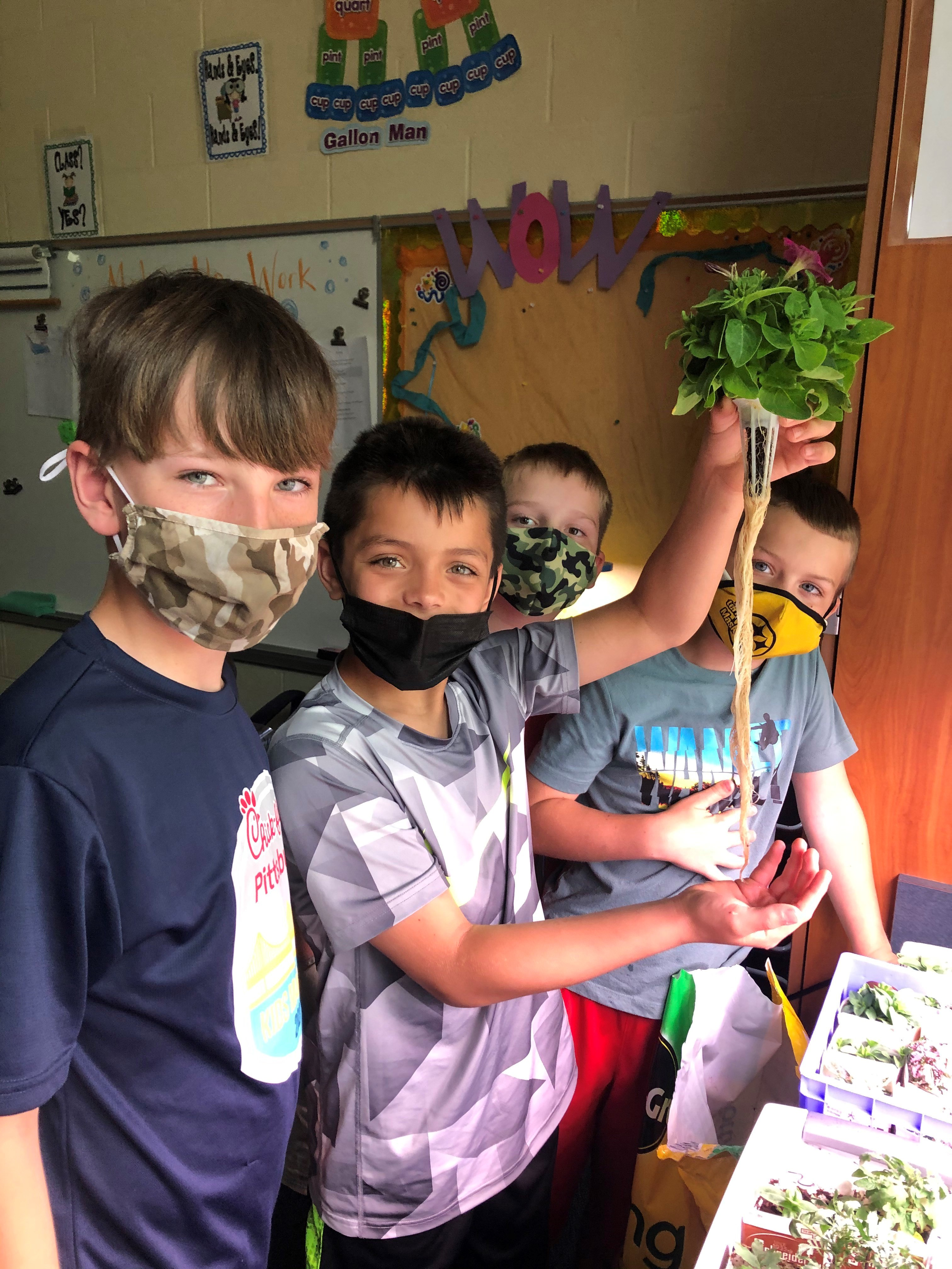 Students displaying a plant grown in class..