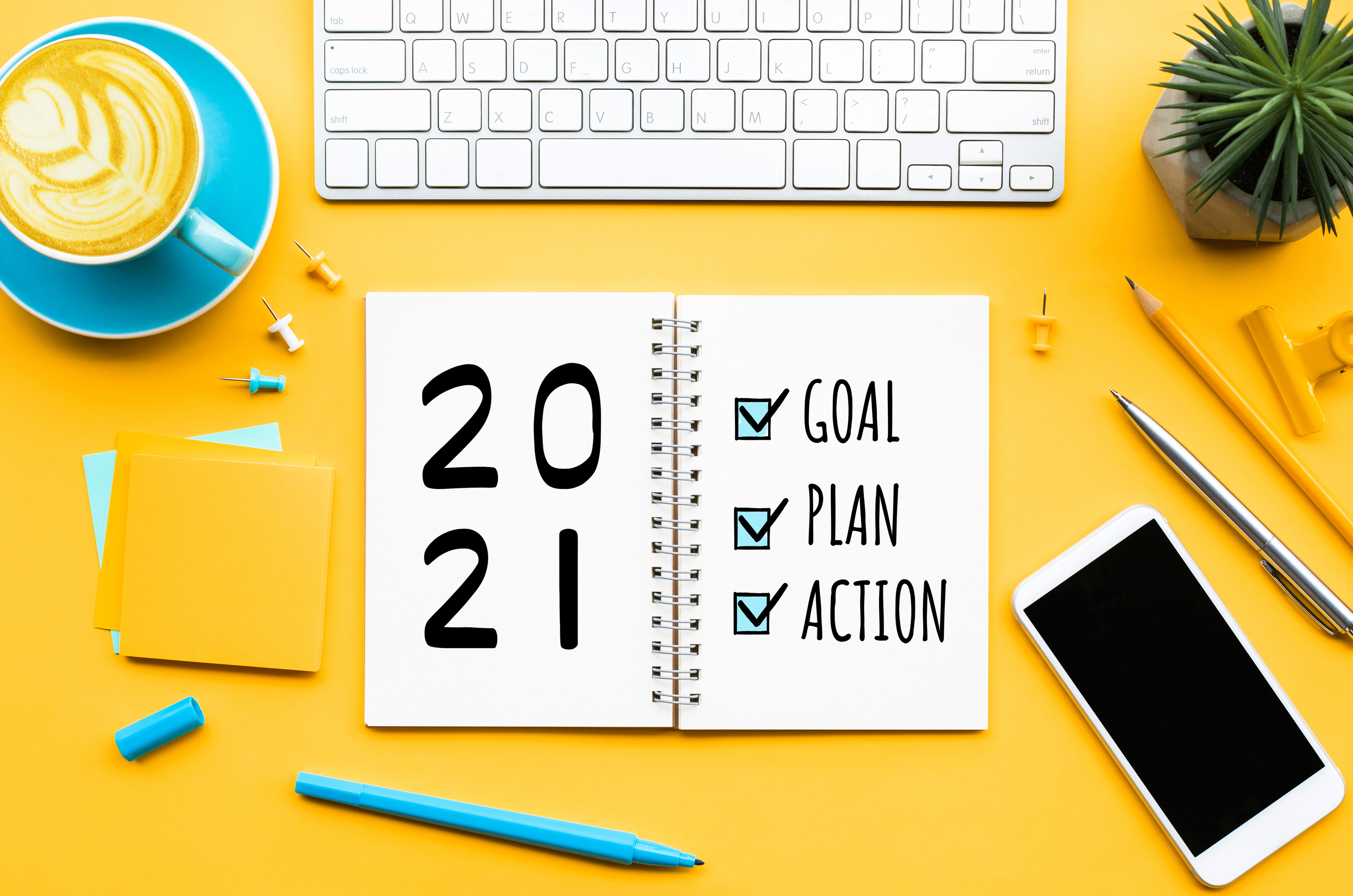 Goal Plan Action 2021 planner on a desk, surrounded by supplies